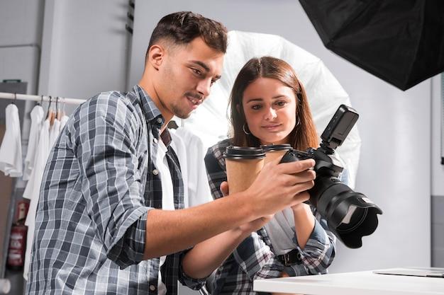 Mujer y hombre mirando fotos en cámara