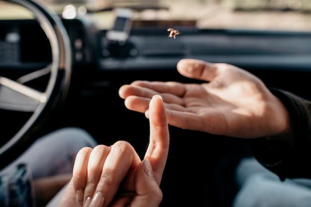 Mujer y hombre mirando un pequeño insecto de cerca
