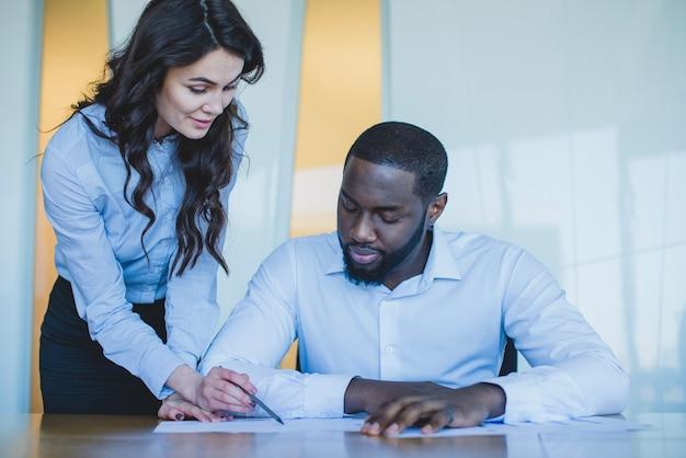 Mujer y hombre de negocios controlando un documento