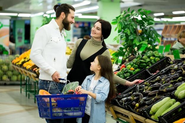 Una mujer con un hombre y un niño, eligiendo verduras mientras compra en un supermercado de verduras