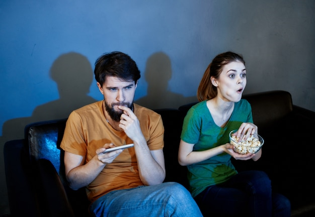Una mujer y un hombre con palomitas de maíz en un sofá de cuero en el interior viendo la televisión por la noche