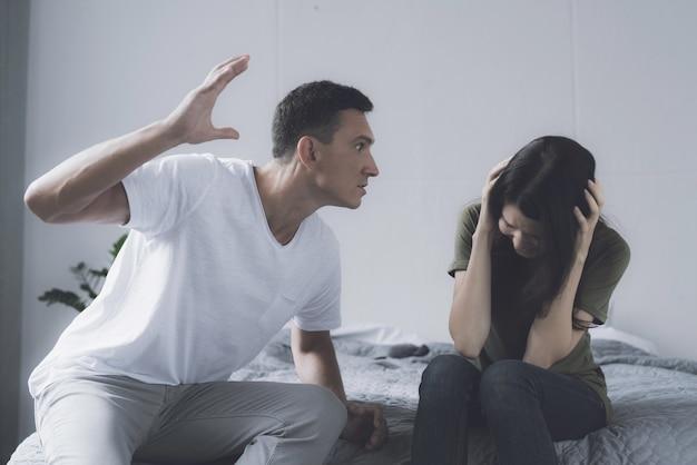 Mujer y hombre pelean mientras está sentado en la cama en su casa
