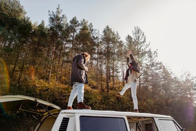 Mujer y hombre de pie en una furgoneta fuera
