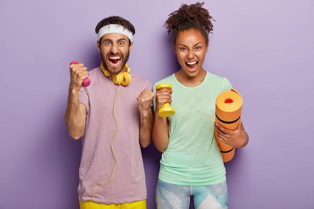 La mujer y el hombre de raza mixta emocional gritan en voz alta, sostienen karemat y pesas, entrenan con el entrenador, gritan de desesperación, están cansados del entrenamiento, aislados en la pared púrpura. gente, deporte, estilo de vida