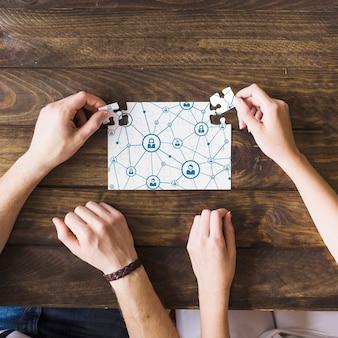 Mujer y hombre resolver rompecabezas de conectividad de red sobre escritorio de madera