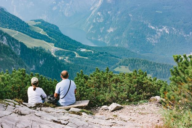 Mujer y hombre sentados y buscando un valle verde de montaña en las montañas alpinas