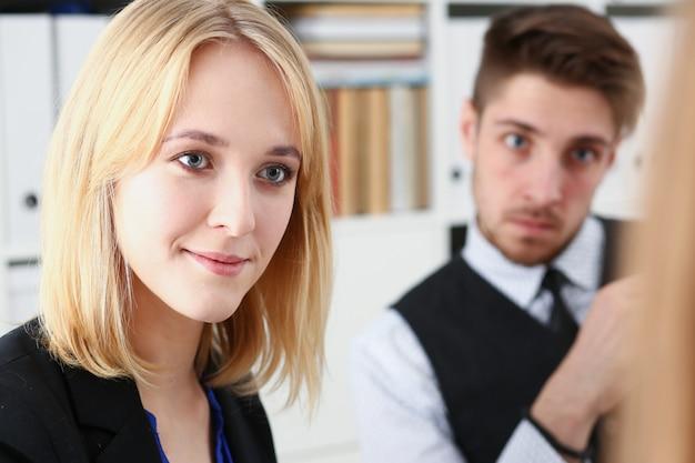 Una mujer y un hombre se sientan en la oficina