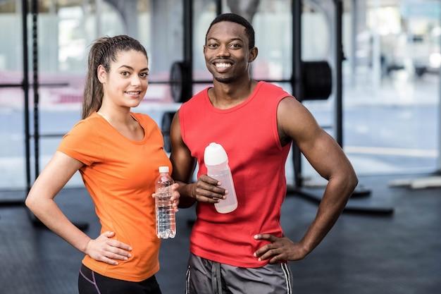 Mujer y hombre sonrientes después de esfuerzo en el gimnasio