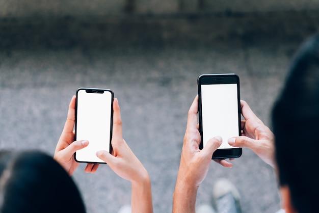 Mujer y hombre sosteniendo un teléfono inteligente, imitan para arriba de la pantalla en blanco. usando un teléfono celular en lifestyl