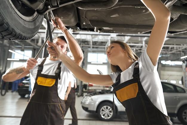Mujer y hombre trabajando en autoservicio como mecánicos.