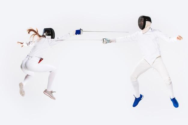 La mujer y el hombre con traje de esgrima practicando con espada contra gris