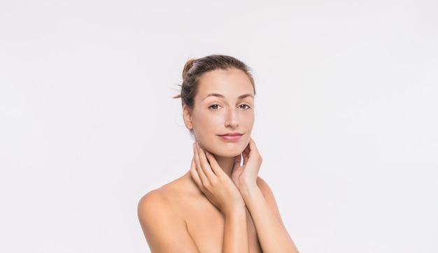 Mujer con hombros desnudos tocando el cuello