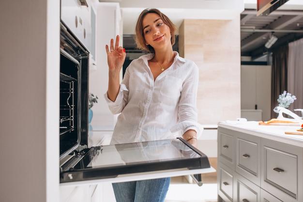 Mujer horneando en la cocina y mirando al horno