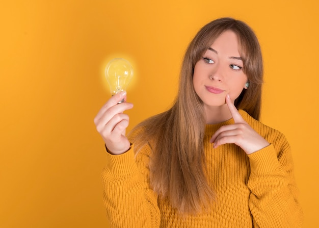 Mujer con una idea, sosteniendo una bombilla sobre fondo amarillo