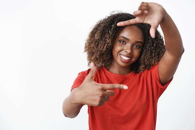 Mujer imaginando cómo aplicar oportunidades a la vida, imaginando la imagen como haciendo un marco con los dedos y mirando a través de ella sonriendo sintiéndose creativa y optimista posando encantada sobre una pared blanca