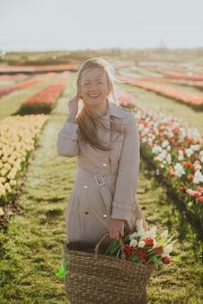 Mujer en un impermeable al amanecer entre las hileras de tulipanes