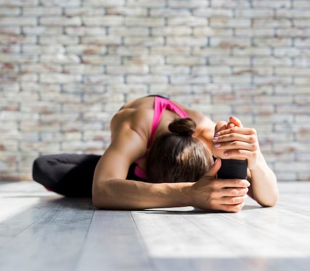 Mujer inclinada al frente mientras estira su pie
