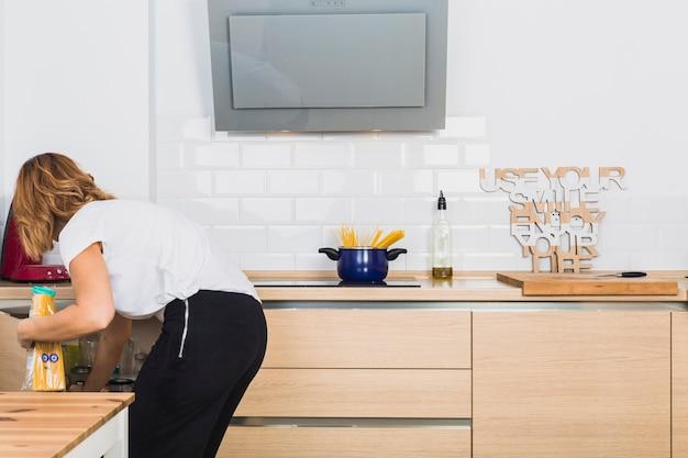Mujer inclinada poniendo comida en el gabinete