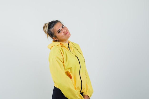 Mujer inclinando la cabeza sobre su hombro en traje deportivo y luciendo linda vista frontal.