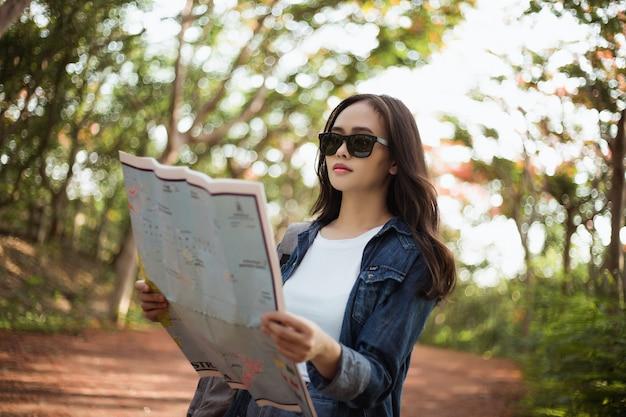 La mujer del inconformista con una mochila está viajando en el verano en la selva de tailandia.