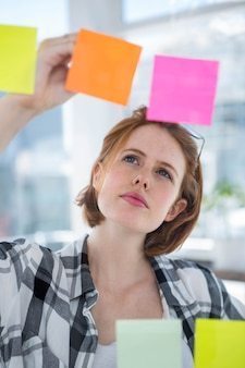 Mujer inconformista pensativa, de pie en su oficina, leyendo notas sobre todo