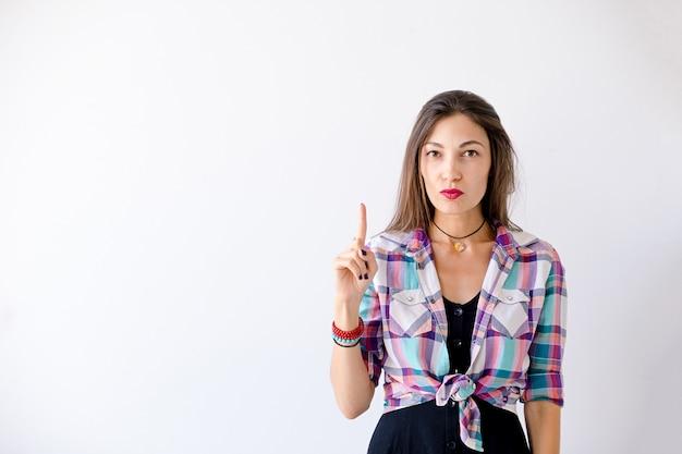 La mujer inconformista tiene una idea apuntando un dedo hacia arriba