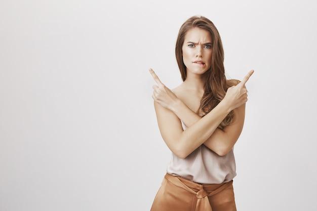 Mujer indecisa con problemas apuntando hacia los lados