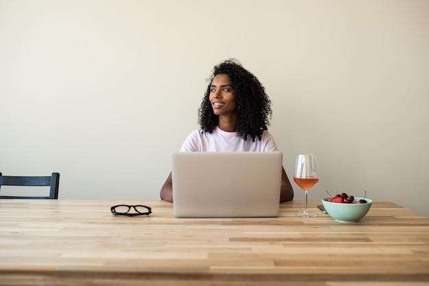 Mujer independiente afroamericana usando laptop en casa