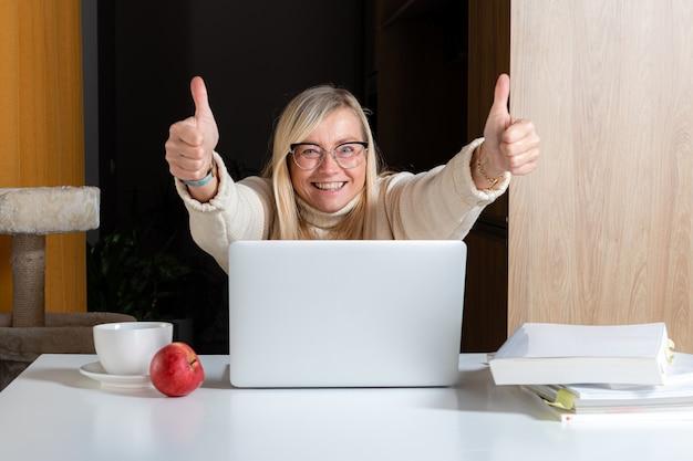Mujer independiente emocional que trabaja en la oficina en casa, sorprendida mirando la pantalla del portátil sorprendida por el correo electrónico recibido, concepto de trabajo desde casa