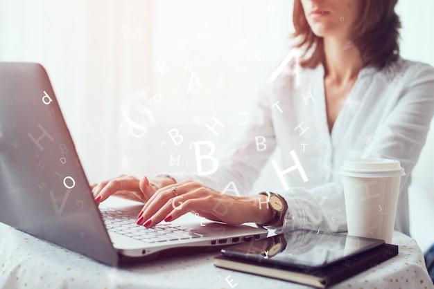 Mujer independiente, estudiante o blogger escribiendo en el teclado sentado en la oficina de la mesa.