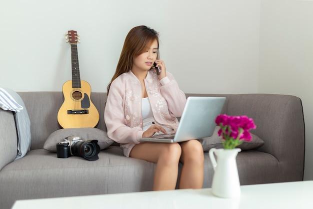 Mujer independiente joven asiática hablando por teléfono inteligente y usando la computadora portátil mientras está sentado en el sofá en casa.