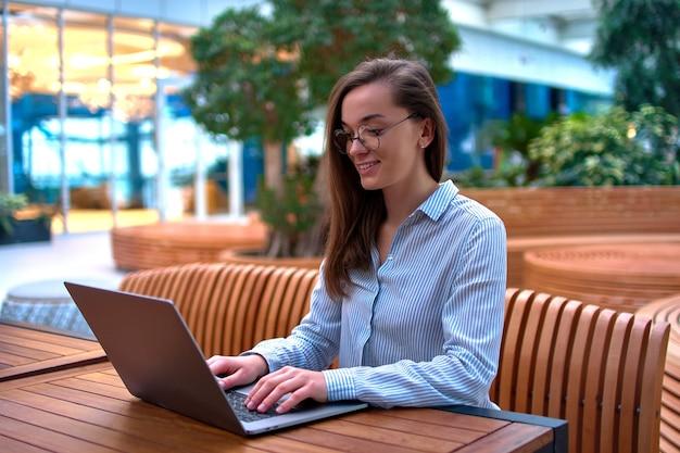 Mujer independiente moderna inteligente trabajando de forma remota en línea en una computadora portátil
