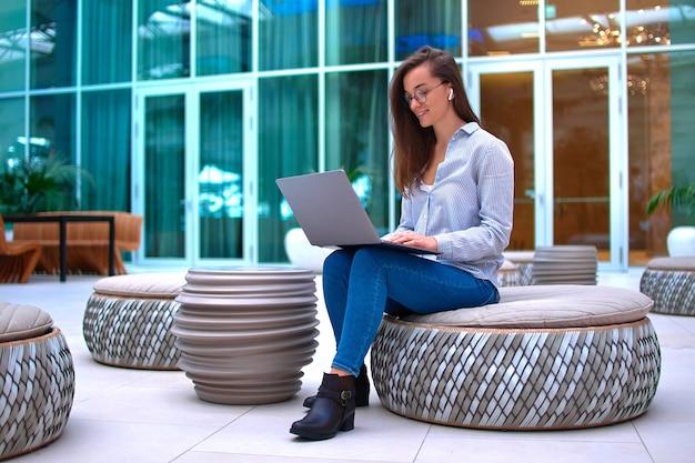 Mujer independiente moderna inteligente trabajando de forma remota en línea en una computadora