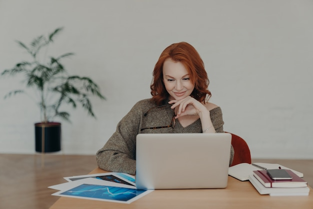 Mujer independiente ocupada sostiene anteojos para la corrección de la visión, posa en el escritorio de su casa