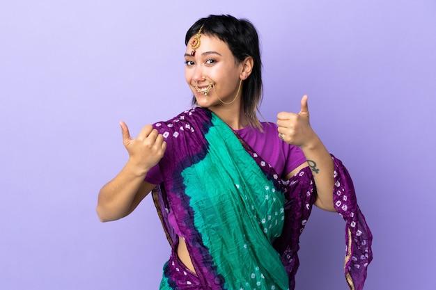 Mujer india aislada en púrpura con pulgares arriba gesto y sonriendo