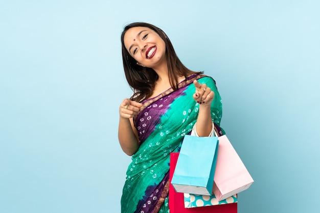Mujer india con bolsas de compras apuntando hacia el frente con expresión feliz