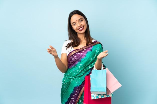 Mujer india con bolsas de compras presentando e invitando a venir con la mano