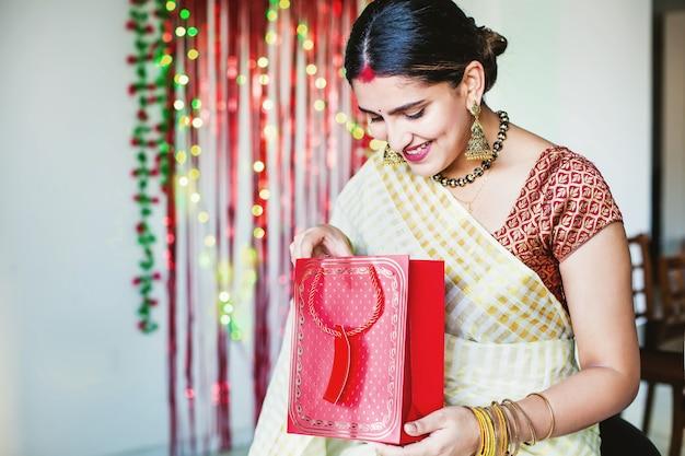 Mujer india casada abriendo un regalo en diwali