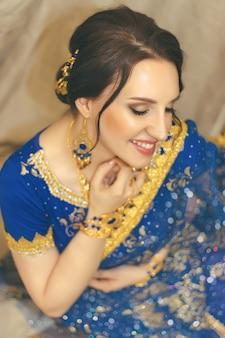 Mujer india cosplay. joven y bella mujer en azul sari indio vestido closeup sobre el fondo marrón multicolor