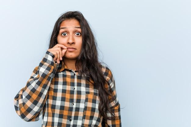 Mujer india fresca joven con los dedos en los labios que mantienen secreta.