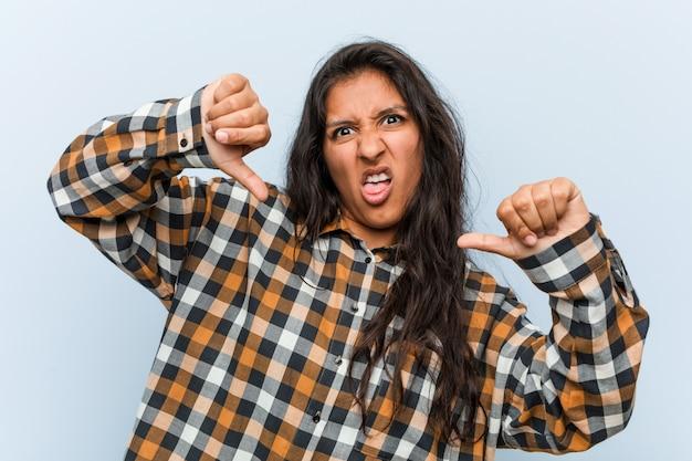 Mujer india fresca joven que muestra el pulgar hacia abajo y que expresa aversión.
