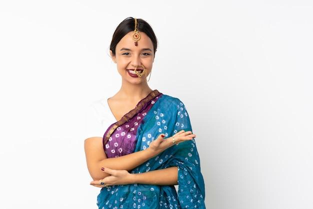 Mujer india joven aislada en la pared blanca que presenta una idea mientras mira sonriente hacia