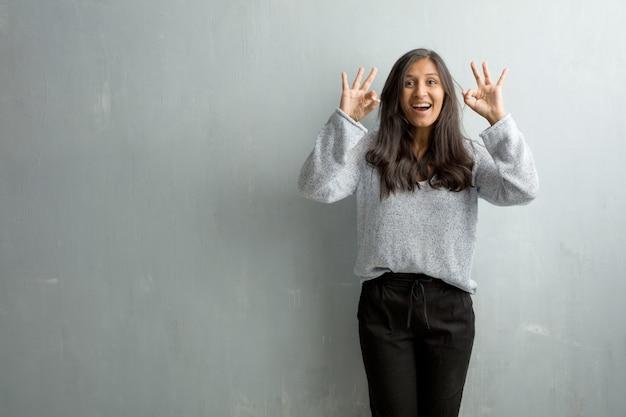 Mujer india joven contra una pared del grunge alegre y confiada que hace el gesto aceptable, emocionado y gritando, concepto de aprobación y éxito