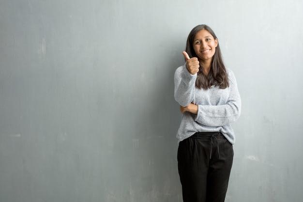 Mujer india joven contra una pared del grunge alegre y emocionada