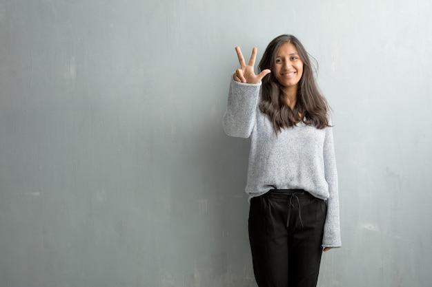 Mujer india joven contra una pared del grunge que muestra el número tres, símbolo de contar