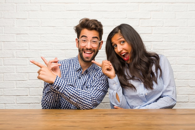 Mujer india joven y pareja de hombres caucásicos apuntando hacia el lado, sonriendo sorprendida presentando algo natural y casual