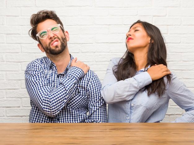 Mujer india joven y pareja de hombres caucásicos con dolor de espalda debido a estrés laboral, cansado y astuto