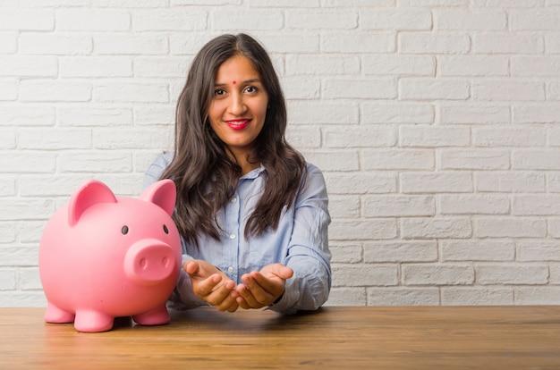 Mujer india joven que sostiene algo con las manos, mostrando un producto, sonriendo y alegre