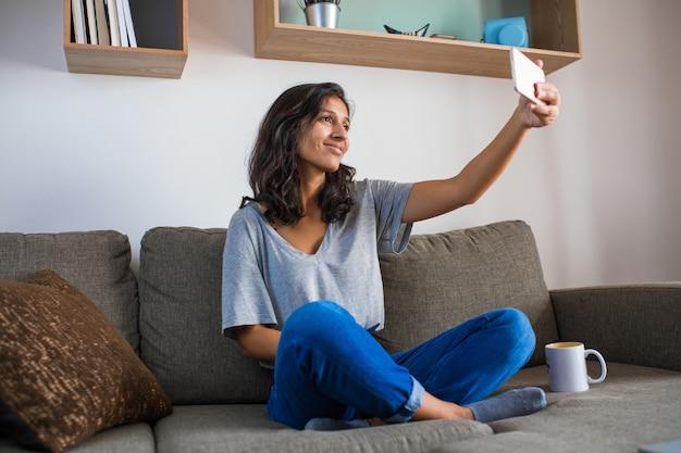Mujer india joven que toma una foto en casa