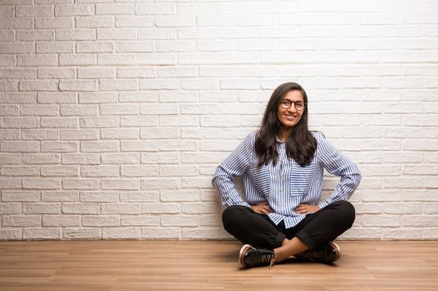 La mujer india joven se sienta contra una pared de ladrillo con las manos en caderas, colocándose, relajado y smil